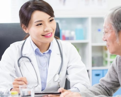 An elderly woman discussing changing Medicare doctors with a medical professional