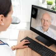 A healthcare professional providing telehealth services to a senior patient