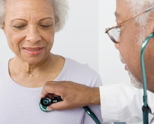A doctor who accepts Medicare Advantage plans checking the heartbeat of a senior woman