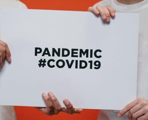 Two medical professionals holding up a clipboard that says pandemic #COVID19