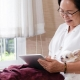 A senior woman snuggling her dog while searching her tablet electronic device for a senior primary care physician