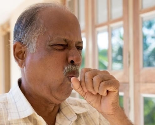 A senior citizen coughing due to his chronic condition, signaling he might qualify for complex care management services