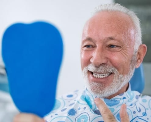 A senior man smiling while gazing into a handheld mirror to admire the results of his elderly dental care services