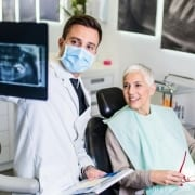 A dentist reviewing x-rays of a patient who is switching dentist offices to a senior dental center