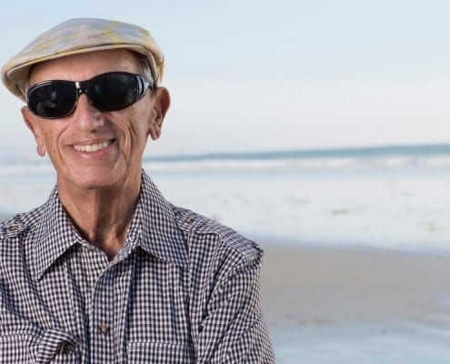 An elderly man smiling to show he's been actively preventing tooth loss in seniors