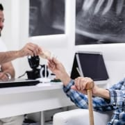 A man paying a discount rate to a dentist for low-cost dental care for seniors